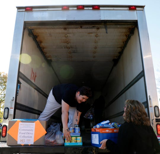 Sam Viscio, left, and Audrea Cordle laugh as they load items for the Lancaster-Fairfield Community Action Agency in the back of a truck Tuesday morning, Oct. 23, 2018, in Lancaster. Viscio, Cordle and other Fairfield County Job and Family Services employees were loading more than 2,000 lbs. of items for the food bank that JFS staff had collected.