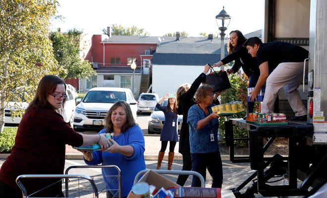 Fairfield County Job and Family Services employees (left to right) Sarah Abner, Sabrina Chabot, Donna Stalter, Aundrea Cordle, Laura Holton, Tina Hall and Sam Viscio load items for the Lancaster-Fairfield Community Action Agency Food Bank into the back of a truck Tuesday morning, Oct. 23, 2018, in Lancaster. JFS staff gathered more than 2,000 lbs. of items for the food bank during a drive they held in earlier this month.
