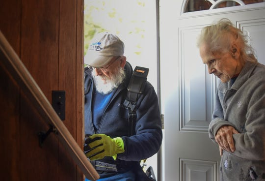 Lois Faggion watches Brian Dollman, a volunteer with Tuesday Toolmen, adjust a doorjam on her newly installed back door, Tuesday, Oct. 23, 2018.  Since the LSJ published a story on the rat problem, a number of people in the community have stepped forward to help the 87-year-old out.