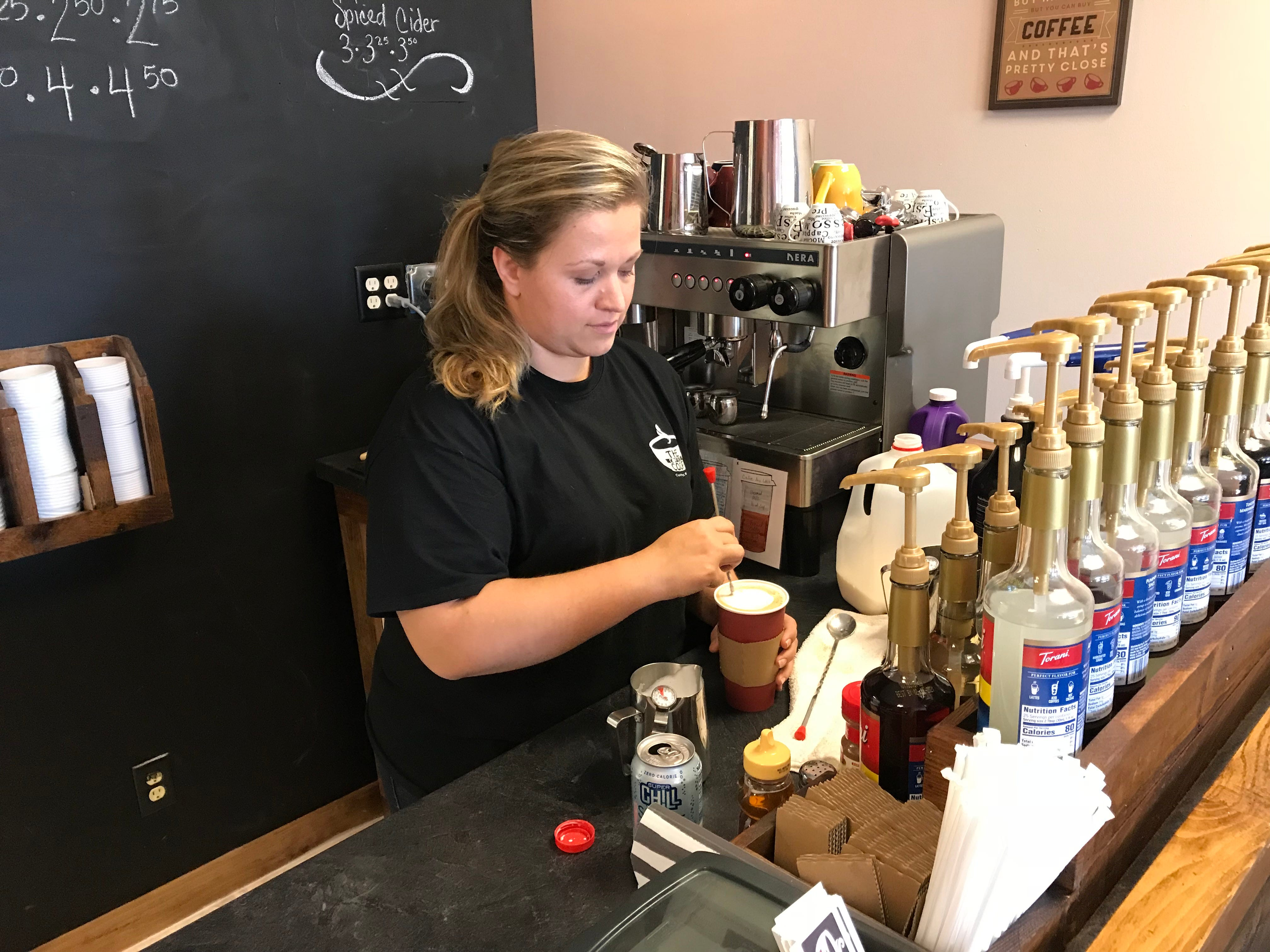 Ariel Oehmichen putting the finishing touches on a white chocolate mocha coffee at The Coffee Coop in Colby.