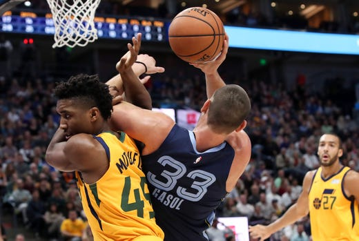 Oct 22, 2018; Salt Lake City, UT, USA; Utah Jazz guard Donovan Mitchell (45) fouls Memphis Grizzlies center Marc Gasol (33) before Gasol can attempt a shot during the first quarter at Vivint Smart Home Arena.
