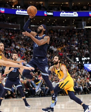 Grizzlies guard Mike Conley gets a shot off past Ricky Rubio during Memphis' win over the Utah Jazz on Monday. The Grizzlies are 2-1 headed into the back half of a two-game road trip against the Kings on Wednesday.