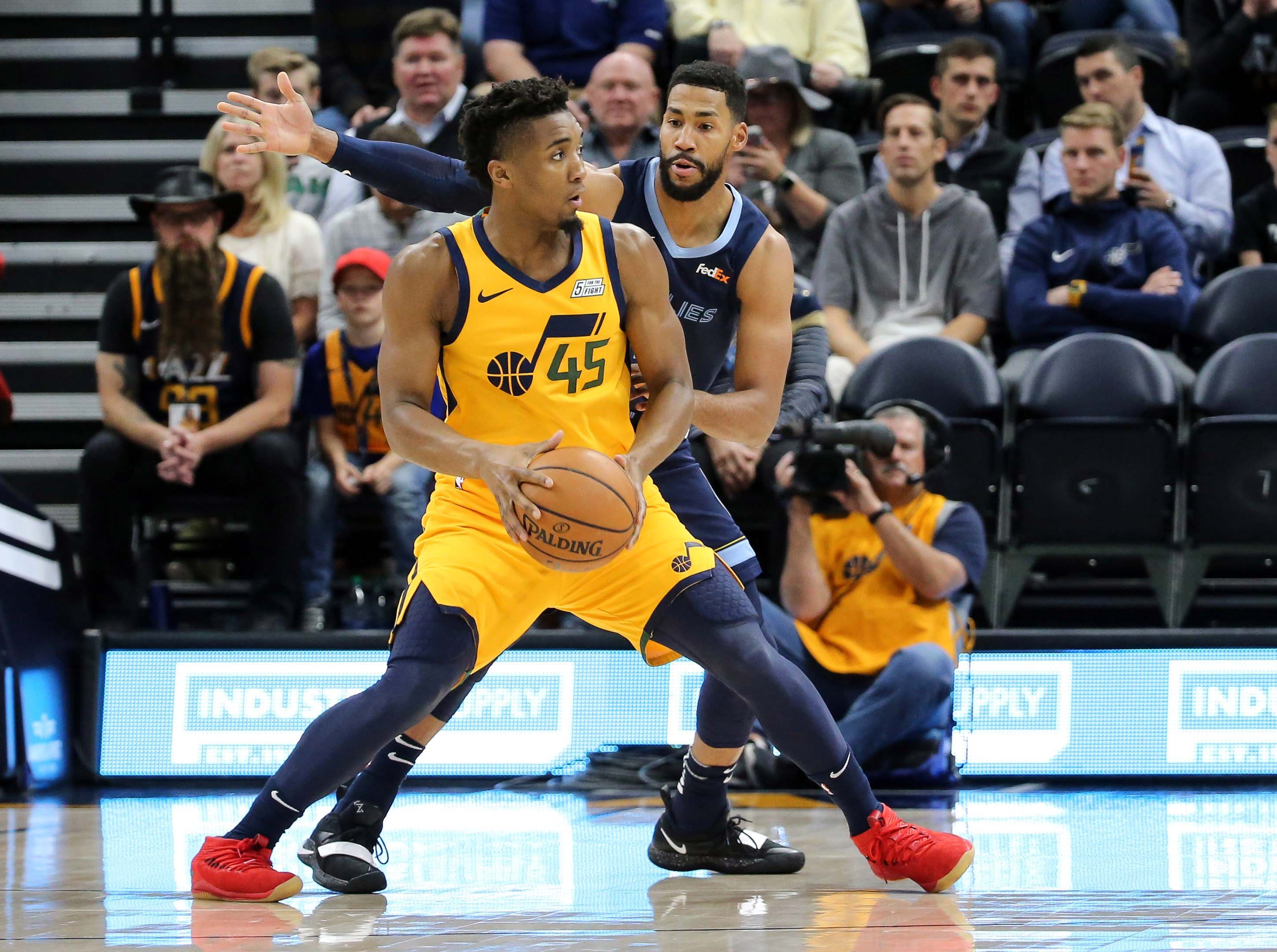 Oct 22, 2018; Salt Lake City, UT, USA; Utah Jazz guard Donovan Mitchell (45) controls the ball and keeps it away from Memphis Grizzlies guard Garrett Temple (17) during the first quarter at Vivint Smart Home Arena.