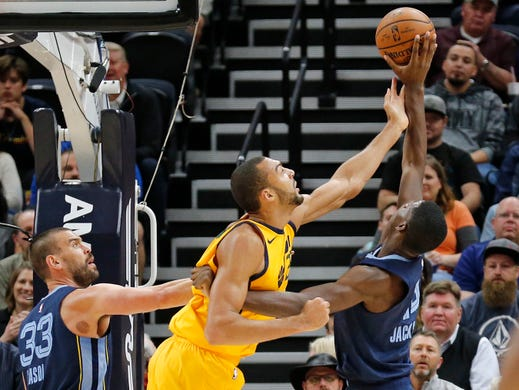 Utah Jazz center Rudy Gobert, center, battles for a rebound with Memphis Grizzlies' Jaren Jackson Jr., right, while Grizzlies' Marc Gasol (33) watches in the first half of an NBA basketball game Monday, Oct. 22, 2018, in Salt Lake City.