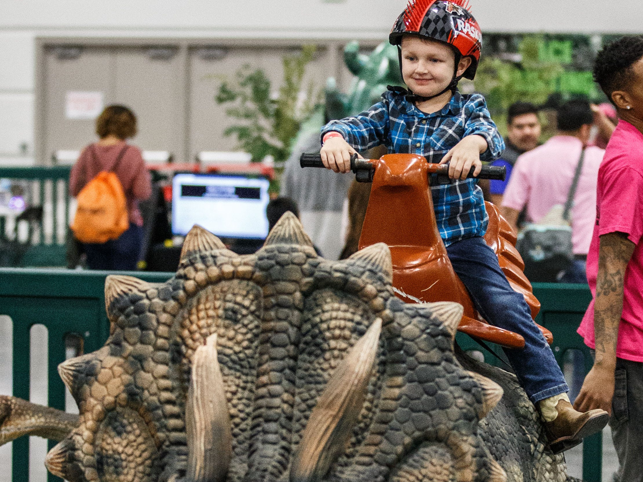 Jaxon Hurth, 4, of Mukwonago rides a dinosaur during his visit to the Jurassic Quest exhibit at Wisconsin State Fair Park in West Allis on Sunday, Oct. 21, 2018. The three-day event featured more than 80 life-sized animatronic dinosaurs, fossils, games, crafts, bounce houses and more.