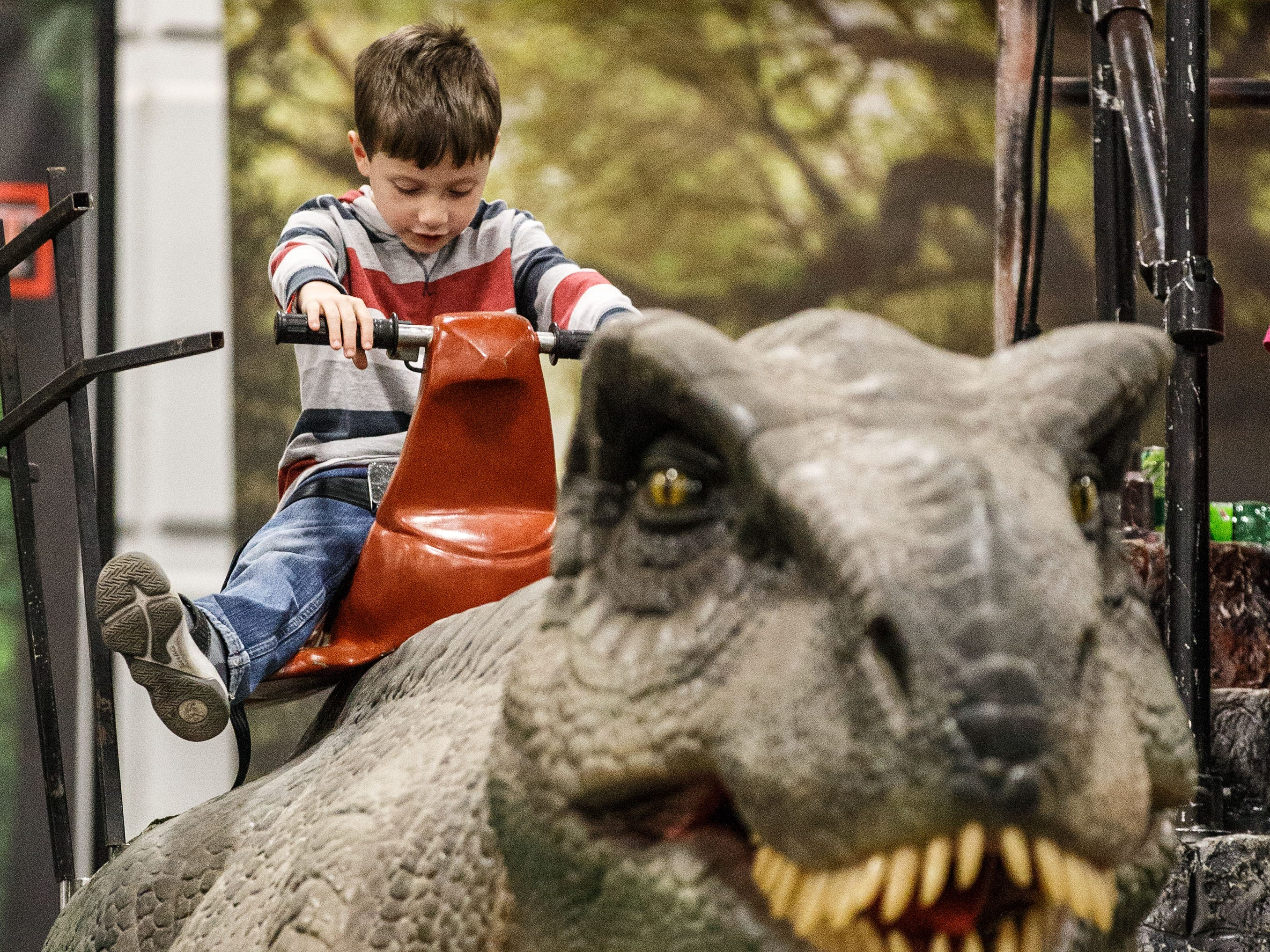 Liam Broz, 6, of Woodstock, IL. rides a life-sized dinosaur during his visit to the Jurassic Quest exhibit at Wisconsin State Fair Park in West Allis on Sunday, Oct. 21, 2018. The three-day event featured more than 80 life-sized animatronic dinosaurs, fossils, games, crafts, bounce houses and more.
