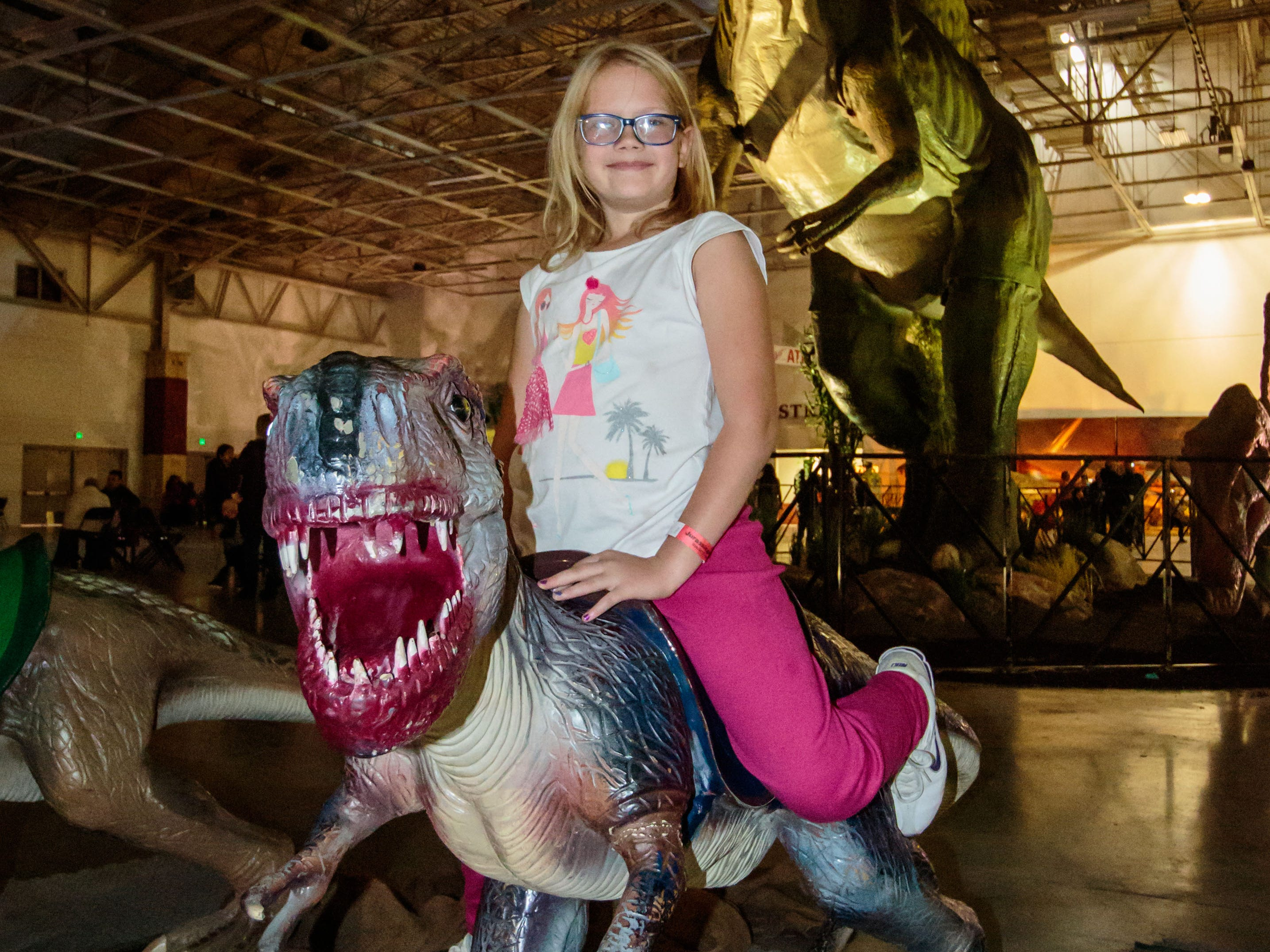 Ellie Fugate, 8, of Union Grove hops aboard a small dinosaur during her visit to the Jurassic Quest exhibit at Wisconsin State Fair Park in West Allis on Sunday, Oct. 21, 2018. The three-day event featured more than 80 life-sized animatronic dinosaurs, fossils, games, crafts, bounce houses and more.