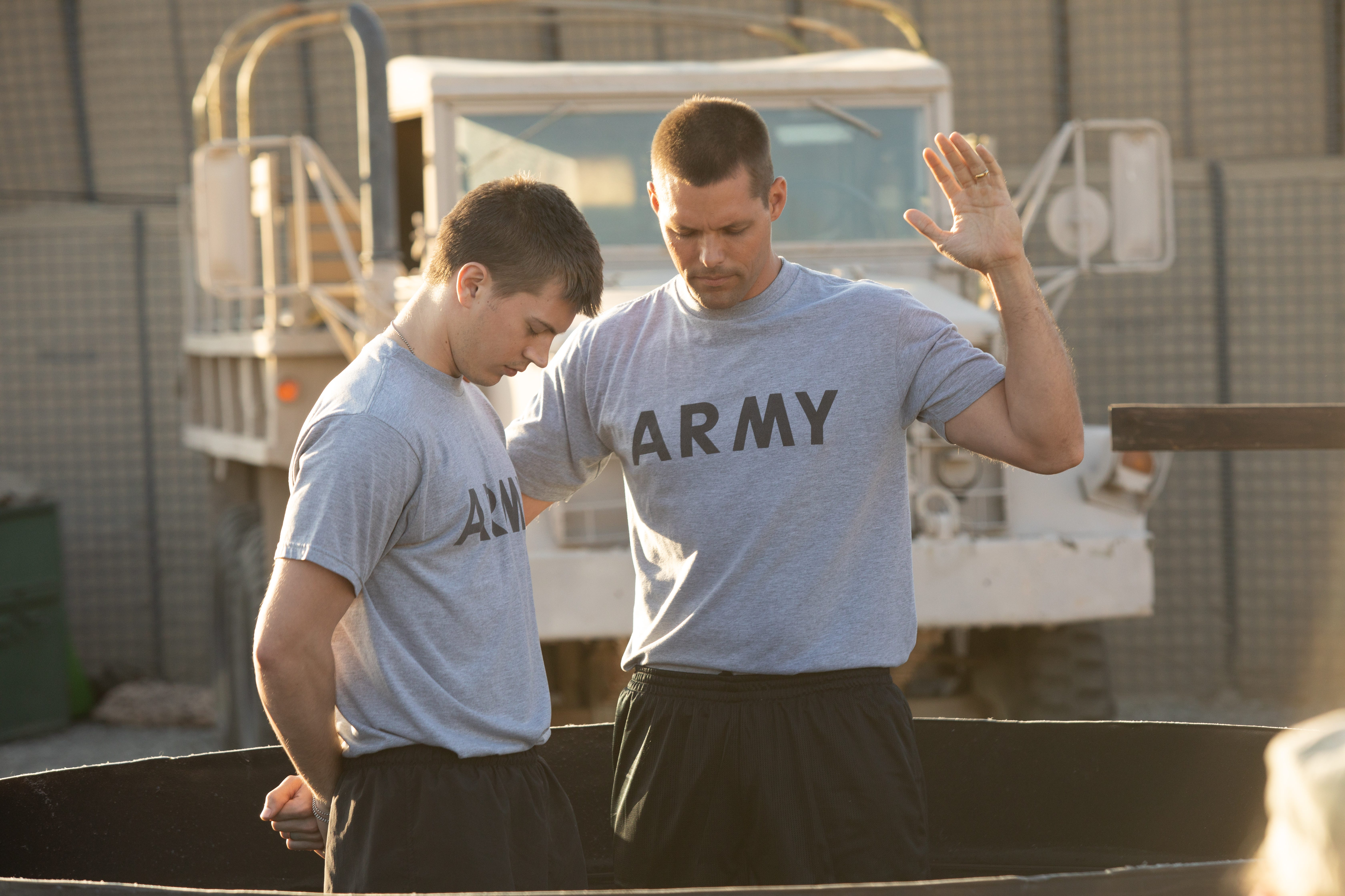 """Chaplain Darren Turner (Justin Bruening) performs an Easter baptism service in Iraq with Lance Bradley (Tanner Stine) in """"Indivisible."""""""