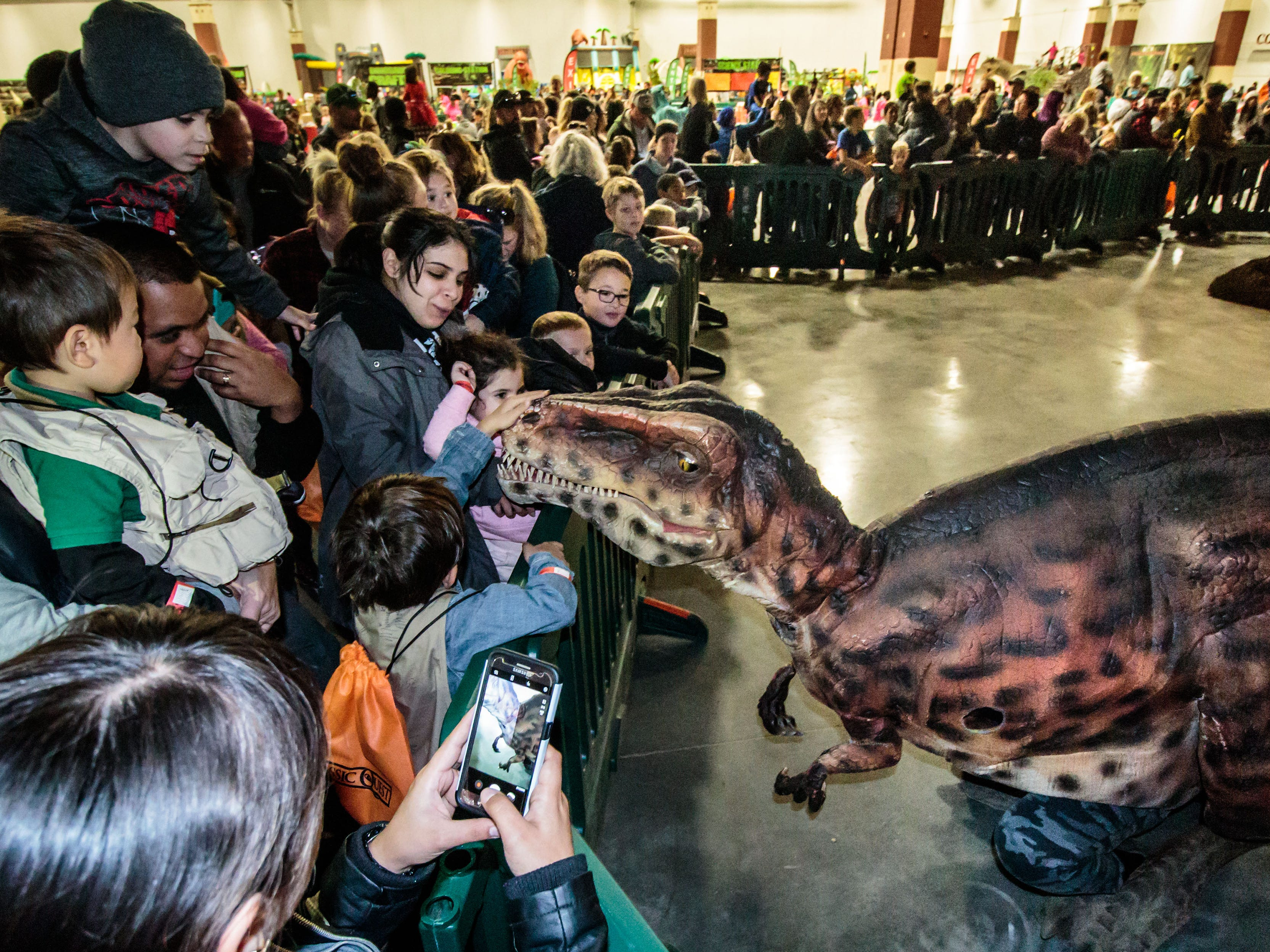 Youngsters gather round to meet Diego the dinosaur during Jurassic Quest at Wisconsin State Fair Park in West Allis on Sunday, Oct. 21, 2018. The three-day event featured more than 80 life-sized animatronic dinosaurs, fossils, games, crafts, bounce houses and more.