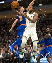 Khris Middleton of the Bucks ducks under the Knicks' Mario Hezonja.