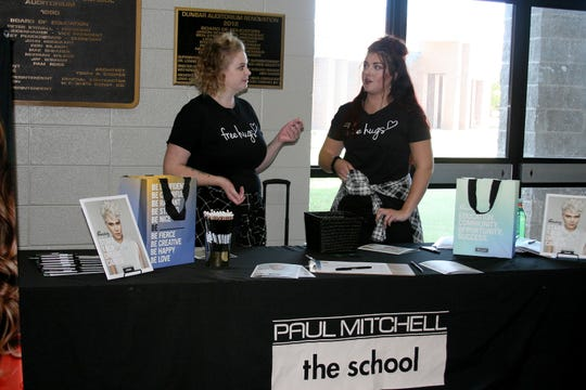 Sarah Poteete (left), a school education leader with Paul Mitchell the School in Fayetteville, and future professional Madalyn Roussel, both of Fayetteville, were among several trade school representatives that attended Tuesday afternoon's Mountain Home High School College Fair in Dunbar Auditorium.