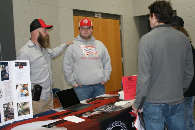 Jonathan Humphrey (left), recruiter/owner of United Welding Institute in Pottsville, and pupil Payton Porter, talk to seniors attending Tuesday's Mountain Home High School College Fair in Dunbar Auditorium. Porter is a 2018 graduate of MHHS and is about to complete an intensive, four-month program at United Welding Institute. Once employed, Porter's trade can earn him a six-figure a year salary.