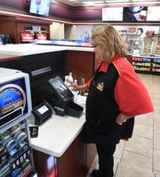 Cashier Regina Massey prints out a handful of Mega Millions tickets for a customer Tuesday afternoon at the Casey's General Store on Highway 5 N in Mountain Home.
