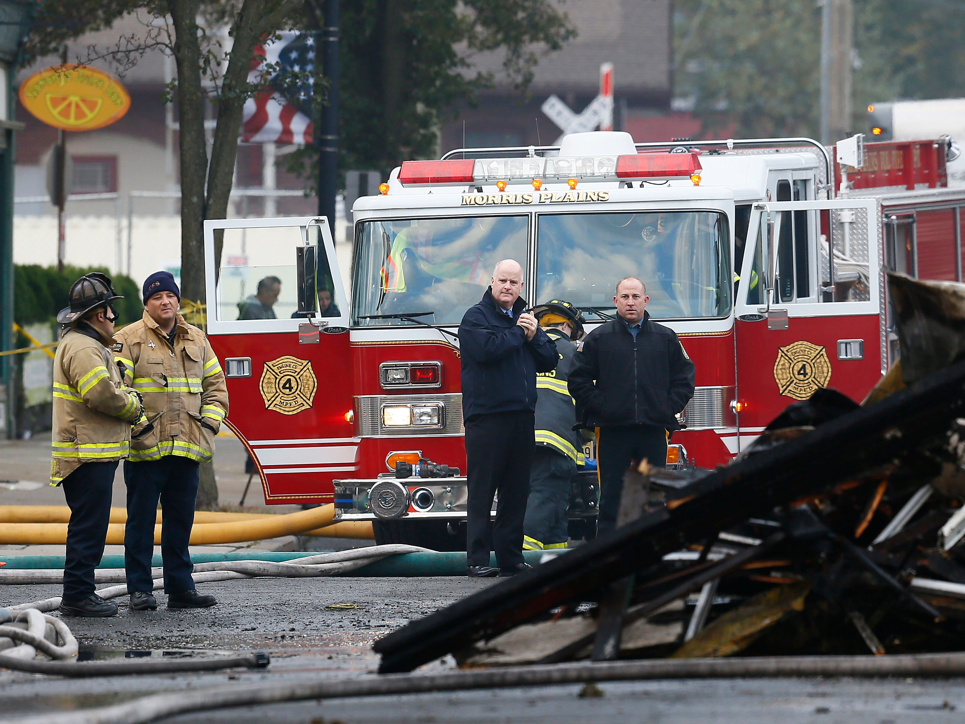 Morris County Sheriff James Gannon, c, at the scene of a devastating fire on North Warren Street in Dover that collapsed multiple businesses in a fast-moving, seven-alarm blaze that officials say started in the basement of Barry's restaurant. The fire then spread throughout the building and to others nearby that contained businesses and apartments Displacing about 100 people from their homes. October 23, 2018, Dover, NJ