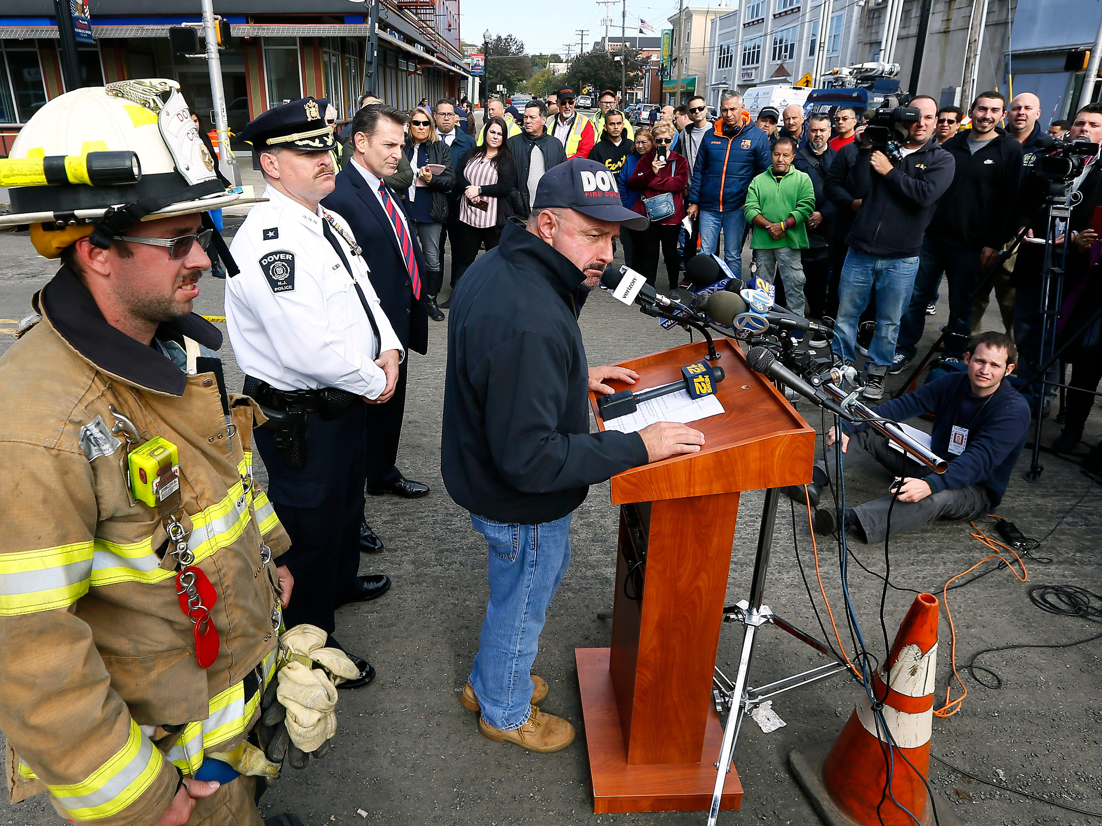 Dover Mayor James P. Dodd, c, speaks to the media and residents supported by Fire Chief Robert Sperry, l, and Police Chief Anthony Smith  the morning after a devastating fire on North Warren Street in Dover that collapsed multiple businesses in a fast-moving, seven-alarm blaze that officials say started in the basement of Barry's restaurant. The fire then spread throughout the building and to others nearby that contained businesses and apartments Displacing about 100 people from their homes. October 23, 2018, Dover, NJ
