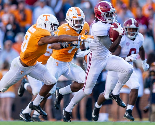 Alabama wide receiver Jerry Jeudy (4) tries to elude Tennessee defensive back Nigel Warrior (18)  and linebacker Quart'e Sapp (14) in first half action at Neyland Stadium in Knoxville, Tn., on Saturday October 20, 2018.