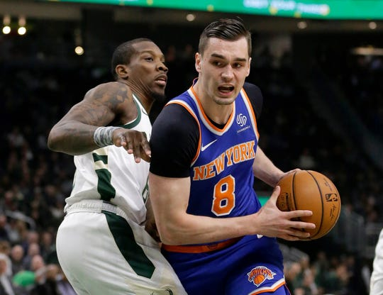 New York Knicks' Mario Hezonja drives to the basket against Milwaukee Bucks' Eric Bledsoe during the first half of an NBA basketball game, Monday, Oct. 22, 2018, in Milwaukee.