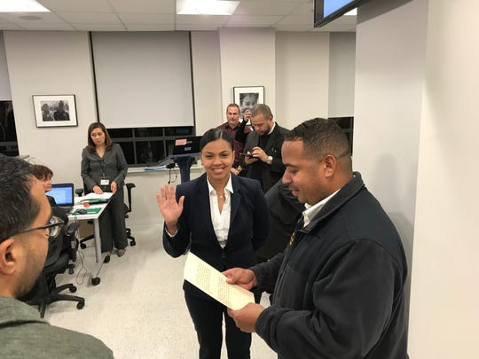 Passaic Mayor Hector Lora reads oath of office to new school trustee Judith Sanchez on Monday night as the school board commissioner she replaces, Salim Patel, looks on.