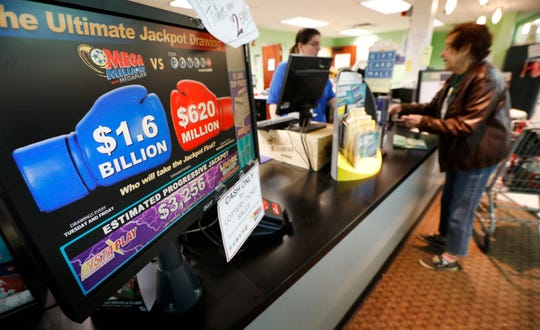 A customer buys a Mega Millions lottery ticket at a local grocery store, Tuesday, Oct. 23, 2018, in Des Moines, Iowa. Lottery players will have a chance at winning an estimated $1.6 billion jackpot in Tuesday night's Mega Millions drawing. (AP Photo/Charlie Neibergall)