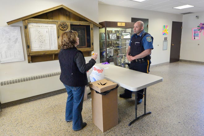 """In this April 2016 file photo, Kathy Statile gets answers to questions from Officer Jose Rodriguez when she brings a bag of unused prescription drugs to the Cedar Grove Police Department for the """"National Prescription Drug Take-Back Day"""" in the lobby of the Cedar Grove Municipal Building."""