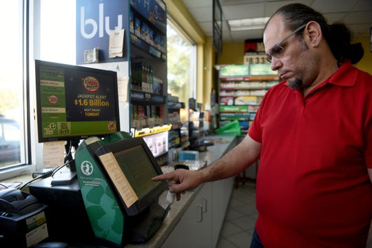 Cashier John Hannah punches tickets purchases for Tuesday's Mega Millions record lottery jackpot of $1.6 billion at the Lukoil on Rt. 23 South in Riverdale on Tuesday, October 23, 2018. Hannah sold the winning ticket at the gas station for the $521 million jackpot drawn on March 30, 2018.