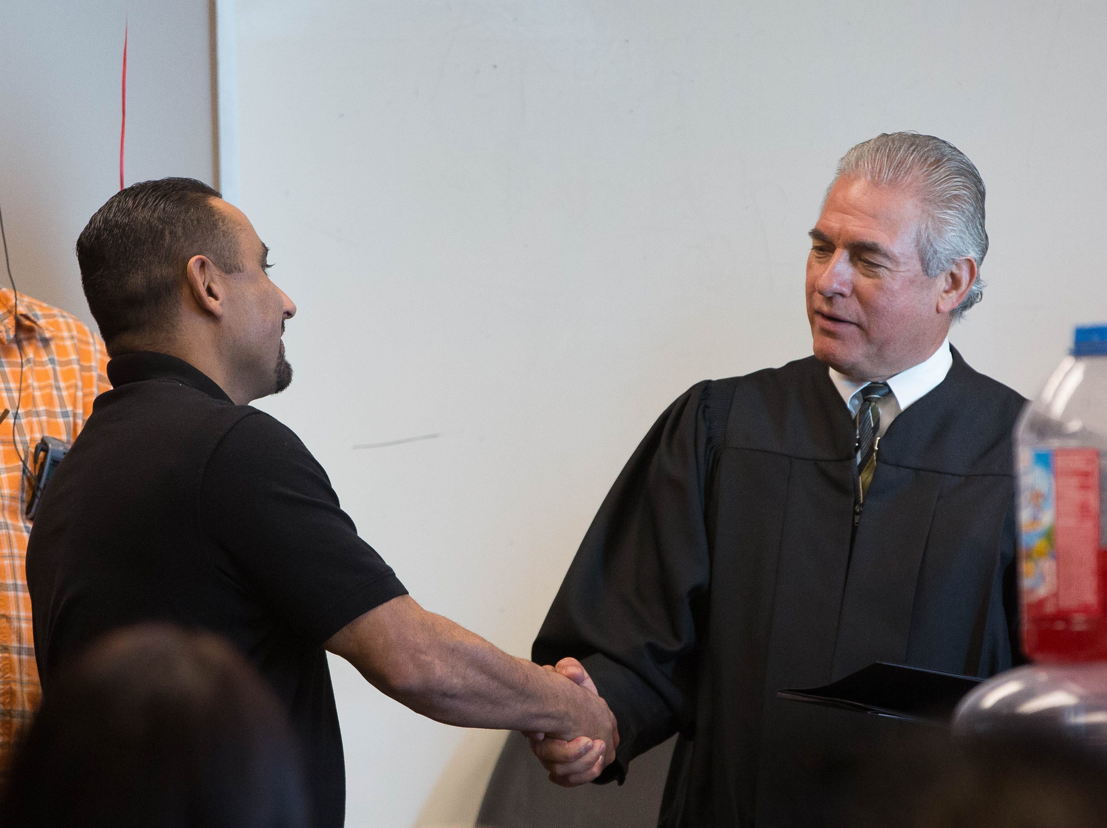 Paul Contreras, a participant in the DWI Drug Court program, shakes hands with Judge Joel Cano, one of two judges presiding over DWI Drug Court, as Contreras graduates from the program, Monday October 22, 2018 at  Doña Ana Magistrate Court.