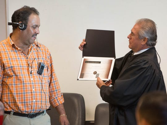 Judge Joel Cano, right, presents Juan Carlos Martinez, left, with a certification of completion of the DWI Drug Court program, Monday October 22, 2018 at  Doña Ana Magistrate court.