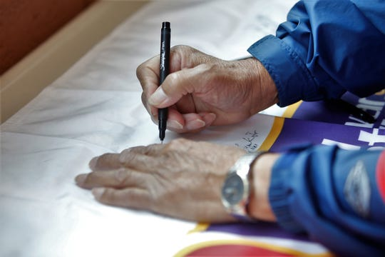 George Howe, a former uranium mill and mine worker, signs a banner for the Cold War Patriots' 10th annual Official National Day of Remembrance on Tuesday at the Phil L. Thomas Performing Arts Center in Shiprock.