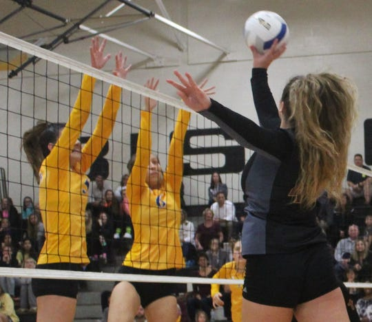 Mercy's senior outside hitter Ella Louissia (44) pushes the ball over the net against a pair of Marian defenders Monday night.