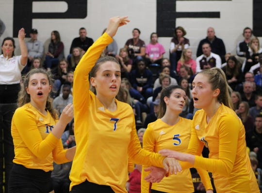 Marian players, led by freshman Ava Brizard (7), celebrate a point against Mercy in Monday's Catholic League A-B Division championship match.