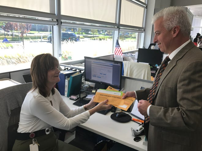 Another absentee ballot is officially received at Westland City Hall by City Clerk Richard LeBlanc (right) and clerk secretary Donna DeWinter.