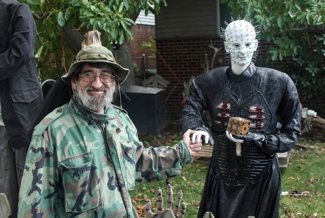Livonia resident Michael Kinney stands with an animatronic Pinhead figurine outside his home on Howell in Livonia. Kinney has amassed a small army of figurines and sets them up each weekend in October.