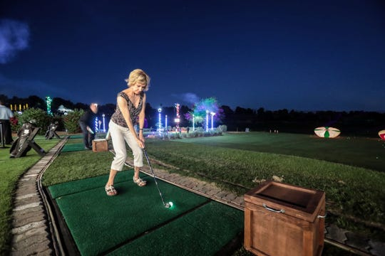 """Jane Gibson of Victoria, British Columbia, hits glowing golf balls at the driving range at Indian Wells Golf Resort on Wednesday, October 17, 2018 during """"Shot in the Night."""" The new attraction has proved popular, officials say."""