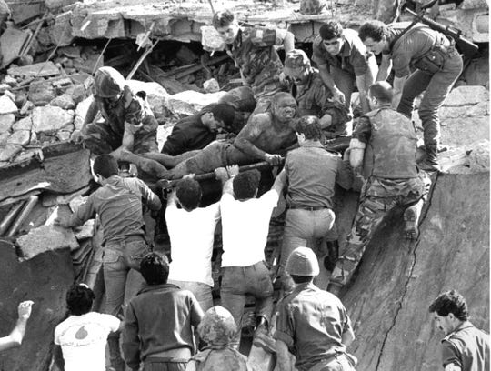 ** FILE ** In a file photo  British soldiers give a hand in rescue operations at the site of the bomb-wrecked U.S. Marine command center near Beirut airport Sunday, Oct. 23, 1983.  Imad Mughniyeh, the militant accused of attacks that left hundreds of Americans and Israelis dead,  has been killed, Hezbollah said Wednesday Feb. 13, 2008.  He was  suspected of masterminding the  attack on Marine base in Lebanon that killed more than 260 Americans in 1983.  (AP Photo/Bill Foley/File)