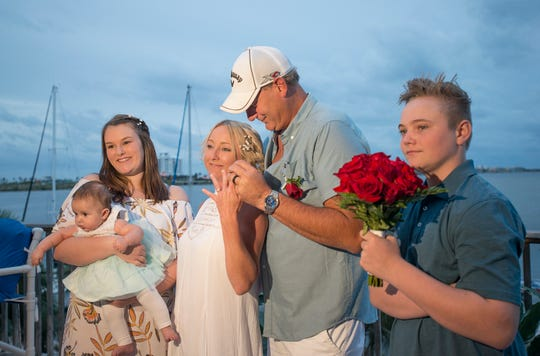 Destiny Pacanins, holding her 3-month-old daughter Eliana, and Jayse Stevenson14, right, join their mother Saya Stevenson and her new husband Brad Barnes as they show off their rings after their wedding ceremony at the Elks Lodge in Pensacola Beach on Monday, October 22, 2018.  The couple evacuated Panama City after Hurricane Michael.