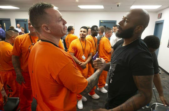 Cardinals defensive back Antoine Bethea shakes hands with inmate Jeremy Schall in the Eagle Point Unit of the Arizona State Prison Complex-Lewis in Buckeye on October 23, 2018. Governor Doug Ducey, Cardinals President Michael Bidwill, Cardinals defensive back Antoine Bethea and defensive lineman Corey Peters toured the Second Chance Center in the prison. The Second Chance Center is working to prepare inmates for their release to find jobs and in other areas to prevent recidivism.