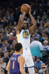 October 22, 2018; Oakland, CA, USA; Golden State Warriors forward Kevin Durant (35) shoots the basketball against Phoenix Suns guard Devin Booker (1) during the third quarter at Oracle Arena. Mandatory Credit: Kyle Terada-USA TODAY Sports