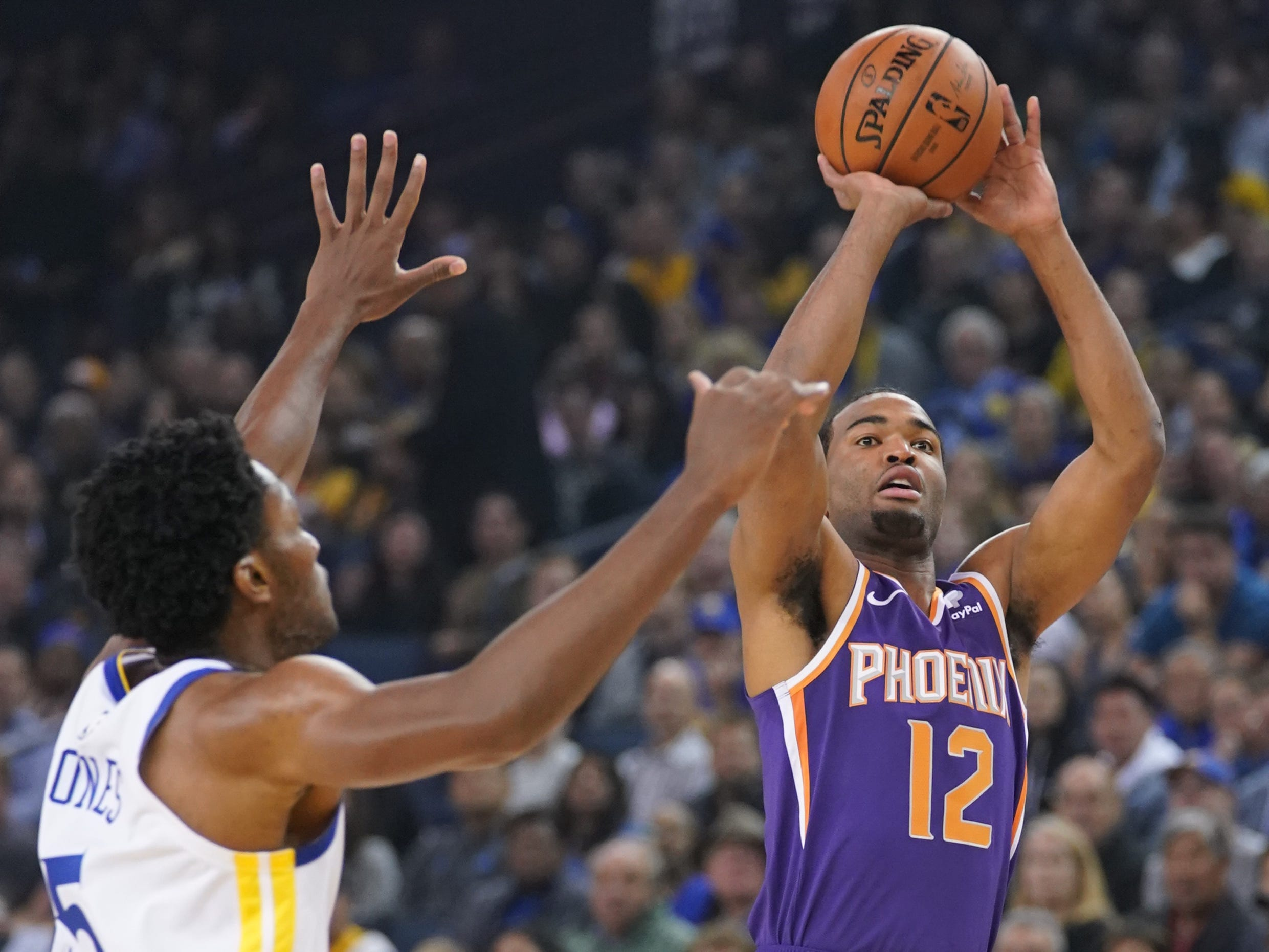 October 22, 2018; Oakland, CA, USA; Phoenix Suns forward TJ Warren (12) shoots the basketball against Golden State Warriors center Damian Jones (15) during the first quarter at Oracle Arena. Mandatory Credit: Kyle Terada-USA TODAY Sports