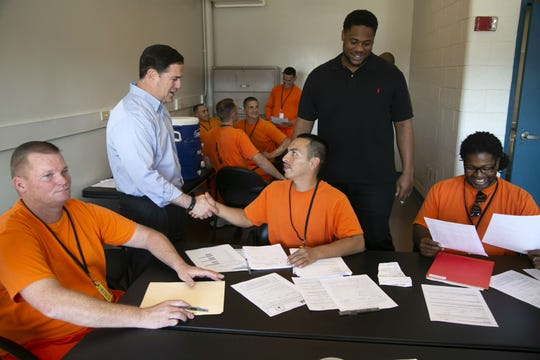 Governor Doug Ducey and Cardinals defensive lineman Corey Peters talk with inmates at a job fair for inmates part of the Second Chance Center in the Eagle Point Unit of the Arizona State Prison Complex-Lewis in Buckeye on October 23, 2018. Governor Ducey, Cardinals President Michael Bidwill, Peters and Cardinals defensive back Antoine Bethea toured the Second Chance Center in the prison. The Second Chance Center is working to prepare inmates for their release to find jobs and in other areas to prevent recidivism.