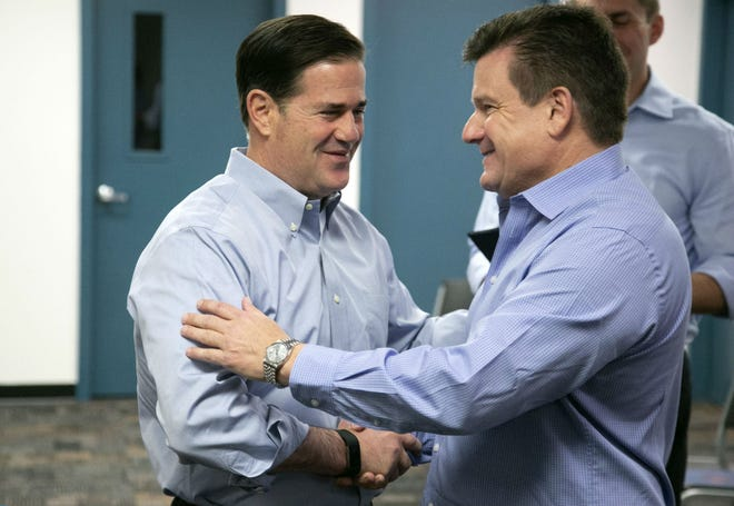 Gov. Doug Ducey (left) shakes hands with Cardinals President Michael Bidwill.