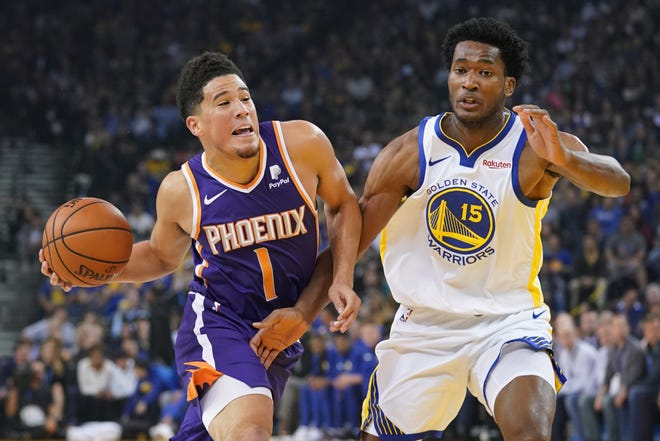 Suns guard Devin Booker works around Golden State center Damian Jones during the first quarter of a game Monday at Oracle Arena.