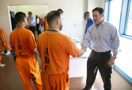 Governor Doug Ducey shakes hands with an inmate at a job fair for inmates part of the Second Chance Center in the Eagle Point Unit of the Arizona State Prison Complex-Lewis in Buckeye on October 23, 2018. Governor Ducey, Cardinals President Michael Bidwill, Cardinals defensive back Antoine Bethea and defensive lineman Corey Peters toured the Second Chance Center in the prison. The Second Chance Center is working to prepare inmates for their release to find jobs and in other areas to prevent recidivism.