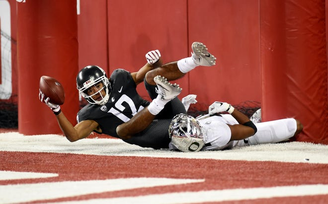 Washington State Cougars wide receiver Dezmon Patmon (12) catches the football for a touchdown against Oregon Ducks cornerback Thomas Graham Jr. (4) in the second half at Martin Stadium. The Cougars won 34-20.