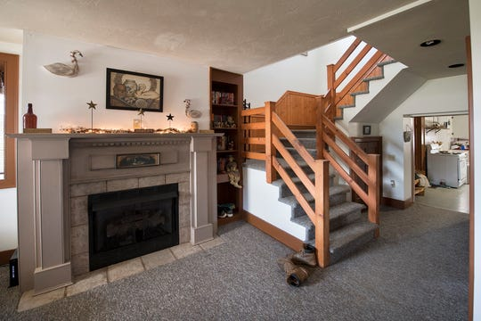 A fireplace and staircase are shown in the living room of the main house at Gray Goose Manor in Springfield Township.