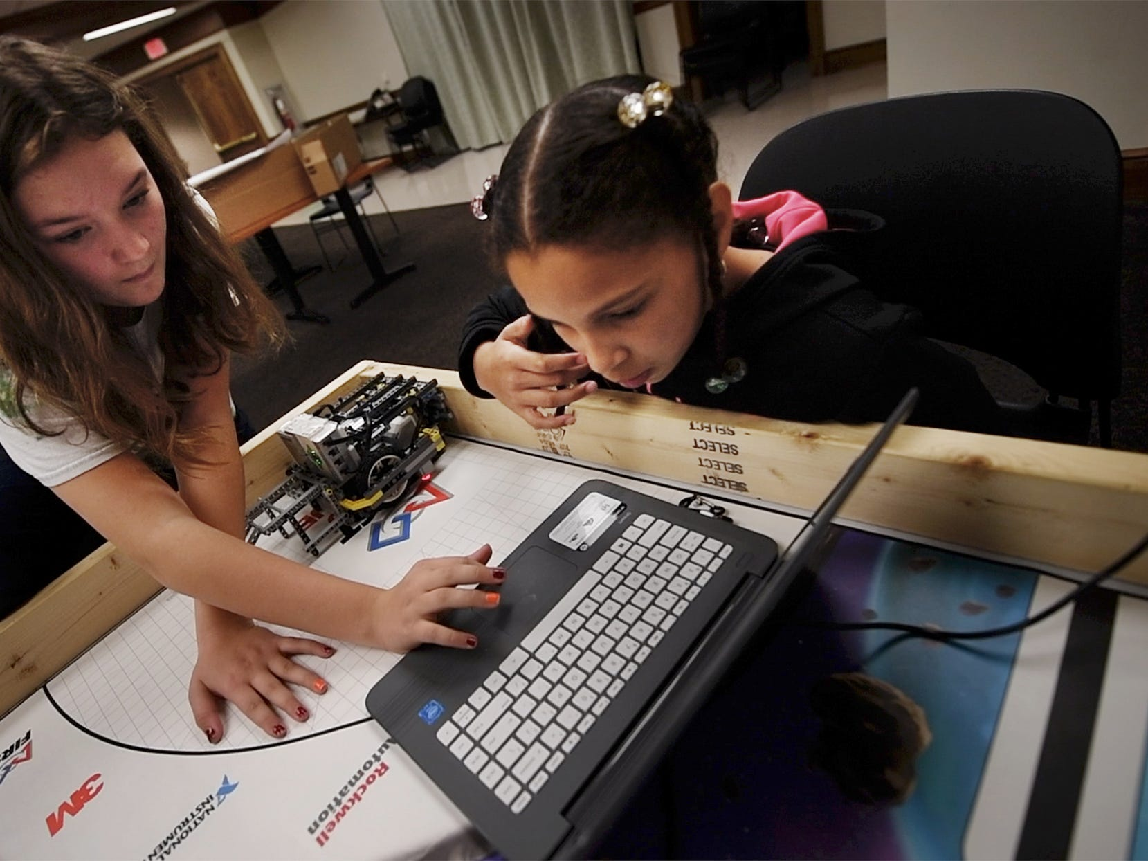 Chloe Broadwater, left, works with Addison Markle programming a robot during a meet with the Young Thinkers of York at Martin Library in York.