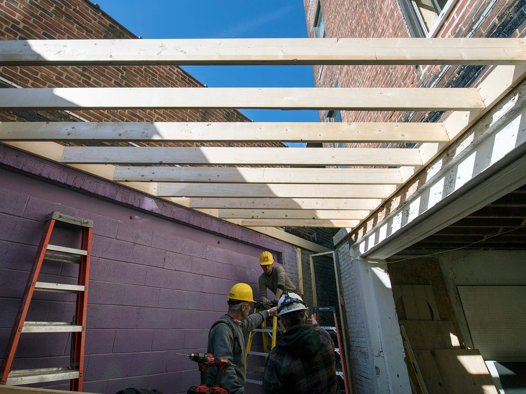 Workers construct a walkway behind the Doll Building at 337 W. Market Street in York.