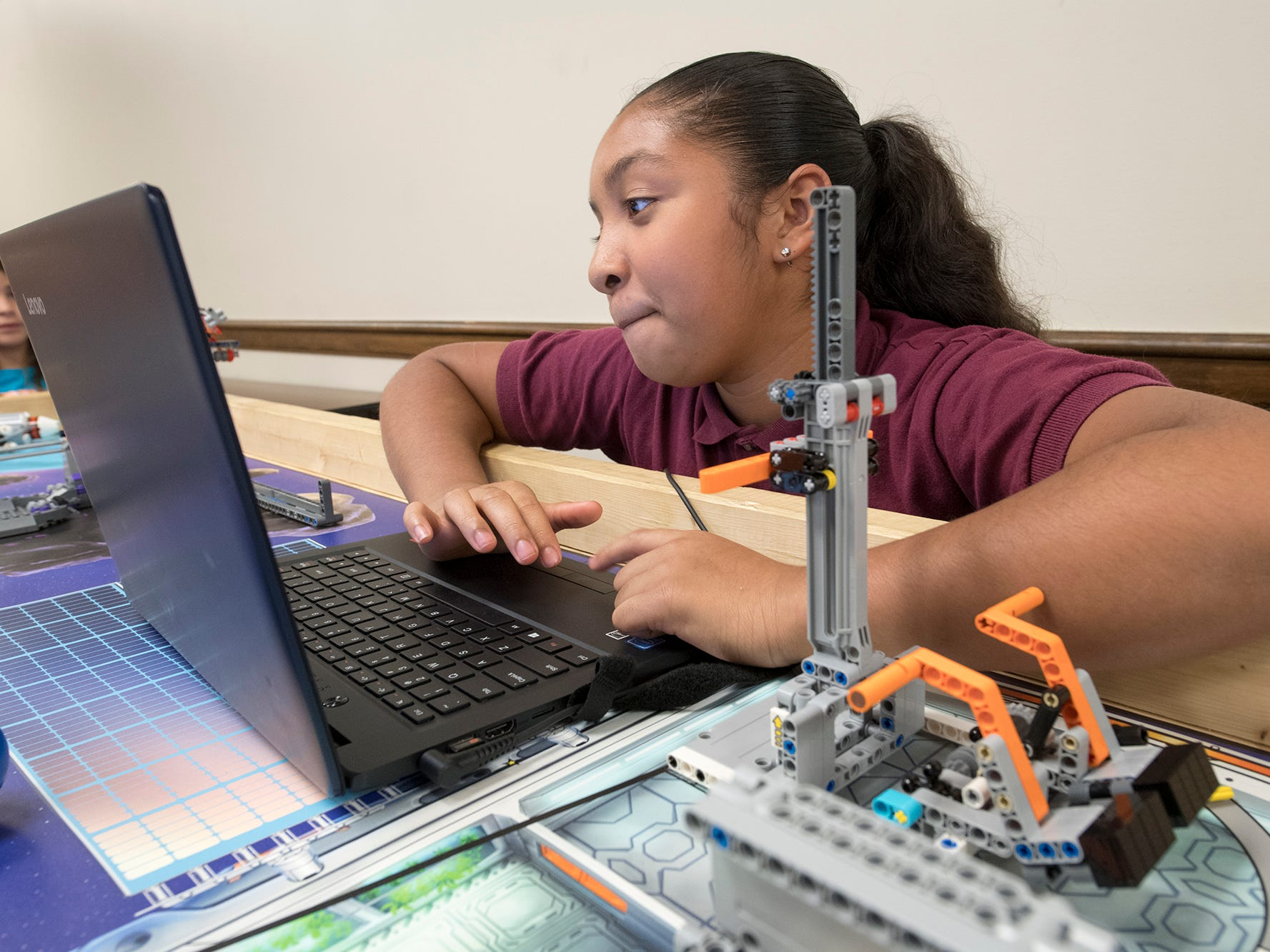 Naigè Kennedy programs a robot using a laptop during the Young Thinkers of York at Martin Library in York.