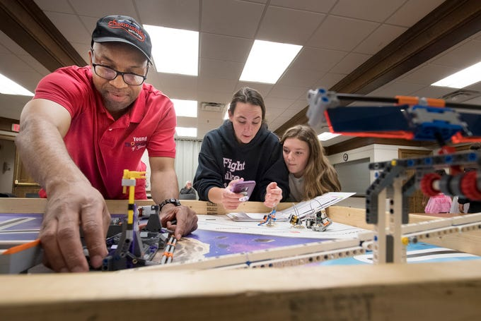 From the left, organizer Ray Ames works with a robot while coach Kim Bowen works with Chloe Broadwater in the background during a meet with the Young Thinkers of York at Martin Library in York.