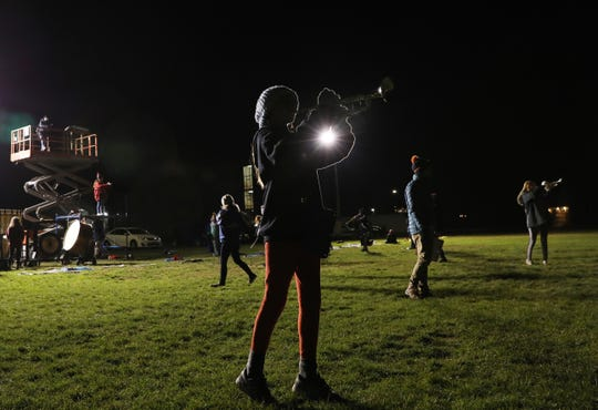 The Greece Blue Knights Marching Band practices under gas-powered pop-up lights in the rear of Odyssey Academy in Greece.