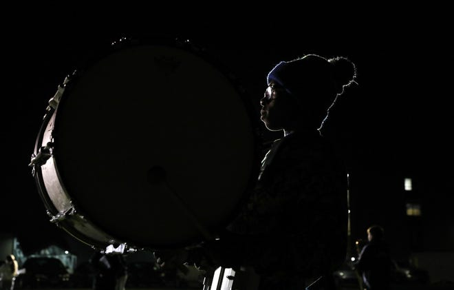 Amir Johnson plays the bass drum as the Greece Blue Knights Marching Band practices under gas-powered pop-up lights in the back of Odyssey Academy in Greece.